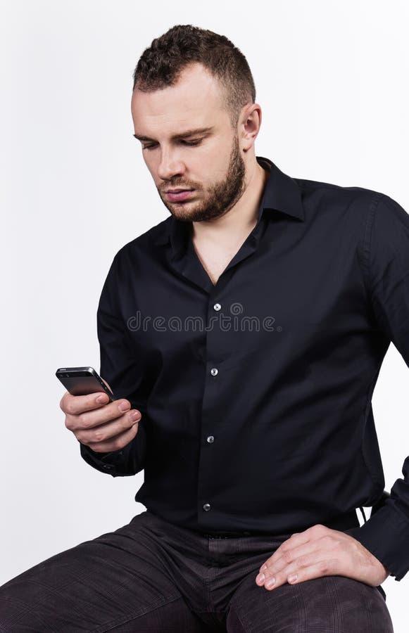 Giovane uomo bello che esamina il suo Smart Phone fotografie stock libere da diritti