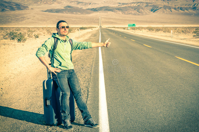 Giovane uomo bello che fa auto-stop nel Death Valley - la California fotografie stock libere da diritti