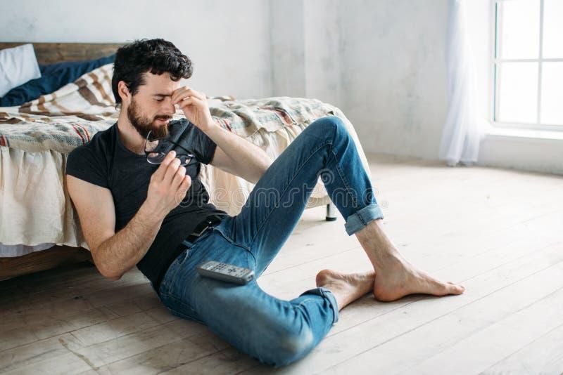 Giovane uomo bello che guarda TV su un pavimento a casa immagini stock
