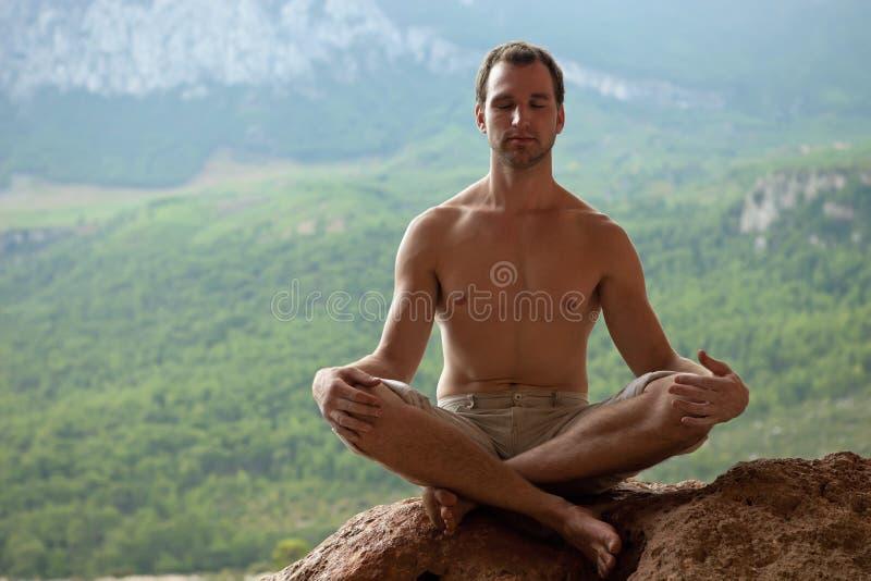 Giovane uomo bello che meditating sulla roccia immagini stock libere da diritti
