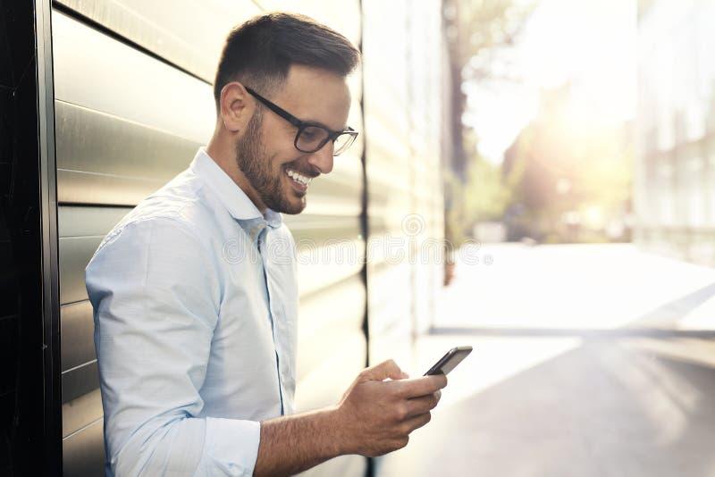 Giovane uomo bello che per mezzo dello Smart Phone immagine stock