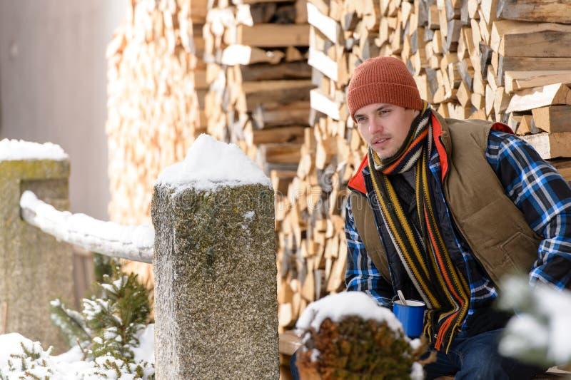 Giovane uomo bello che posa il legno di modo di inverno fotografia stock libera da diritti