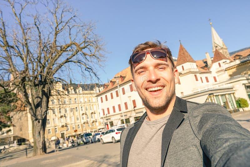 Giovane uomo bello che prende selfie alla vecchia città Tirolo del sud di Meran fotografia stock libera da diritti