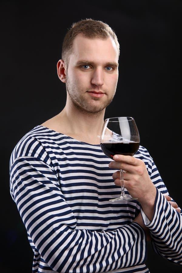 Giovane uomo bello che tiene un vetro di vino immagini stock libere da diritti