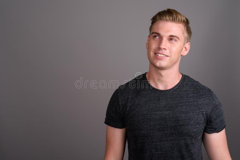 Giovane uomo bello con capelli biondi che portano camicia grigia contro il gr fotografie stock libere da diritti