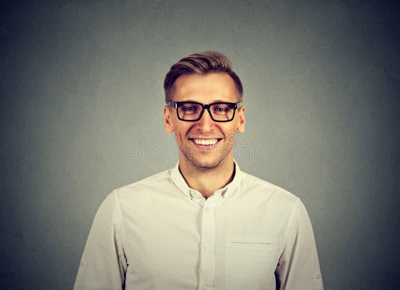 Giovane uomo bello con gli occhiali d'uso di modo di grande sorriso immagine stock