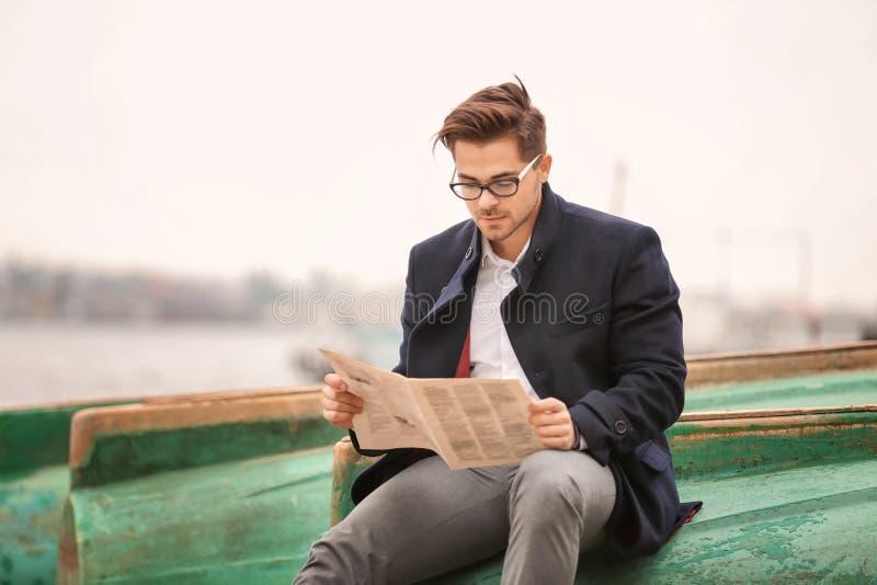 Giovane uomo bello con il giornale che si siede sulla vecchia barca immagine stock libera da diritti