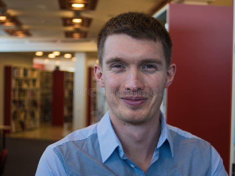 Giovane uomo bello con il grande sorriso contro il fondo neutrale dell'ufficio con i lotti dello spazio della copia fotografie stock libere da diritti