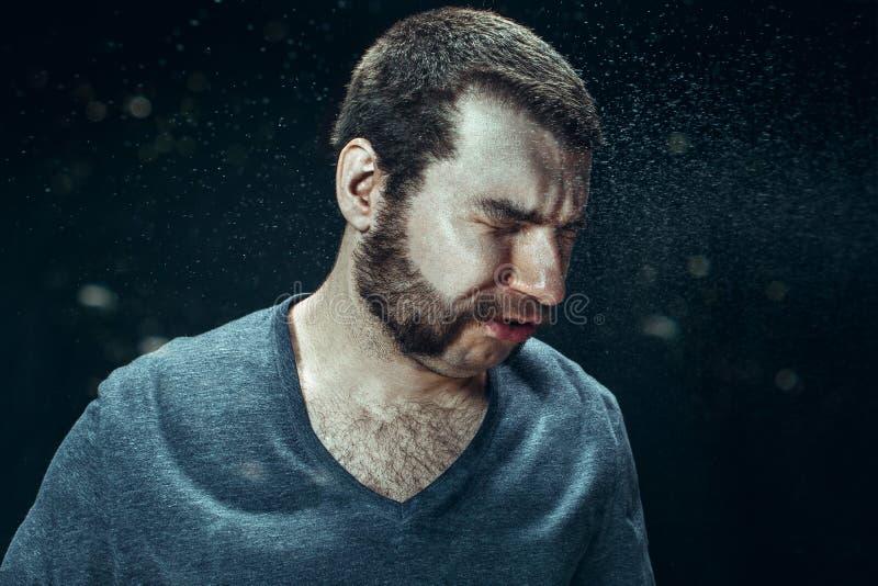 Giovane uomo bello con la barba che starnutisce, ritratto dello studio fotografia stock
