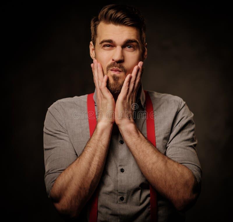Giovane uomo bello con le bretelle d'uso della barba e posare sul fondo scuro fotografie stock