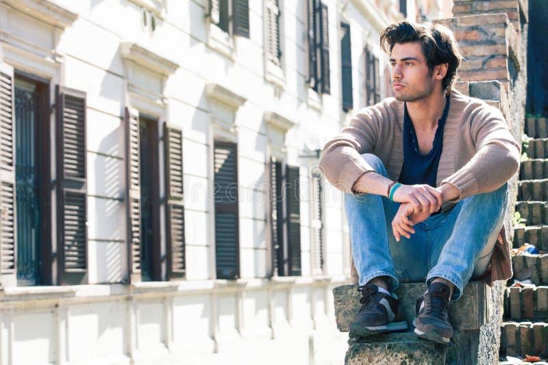Giovane uomo bello della città Modello di seduta urbano Costruzione Windows immagine stock