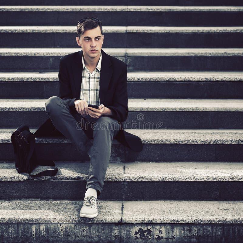 Giovane uomo bello di affari che per mezzo dello Smart Phone sui punti fotografie stock libere da diritti