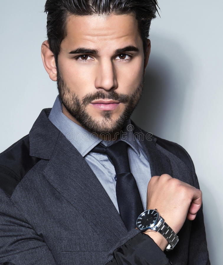 Giovane uomo bello di affari in vestito su fondo grigio immagini stock libere da diritti
