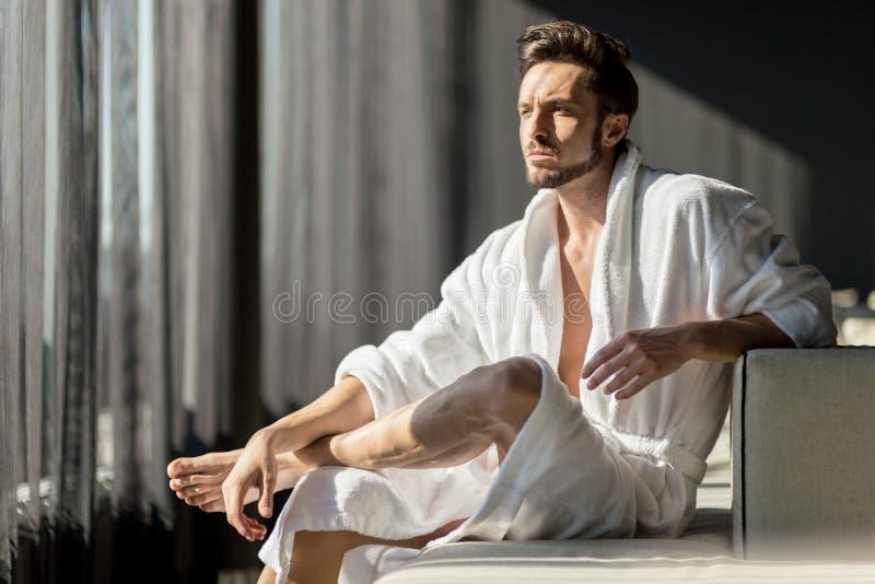 Giovane, uomo bello di mattina che pensa mentre sedendosi in una r fotografia stock