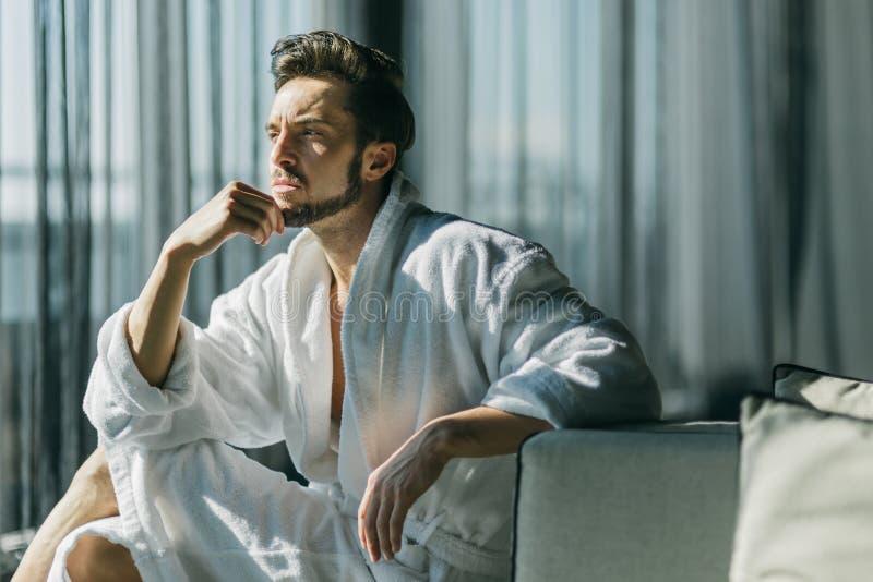 Giovane, uomo bello di mattina che pensa mentre sedendosi in una r fotografia stock libera da diritti