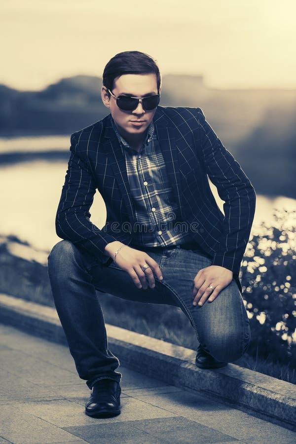 Giovane uomo bello di modo in occhiali da sole al tramonto immagine stock