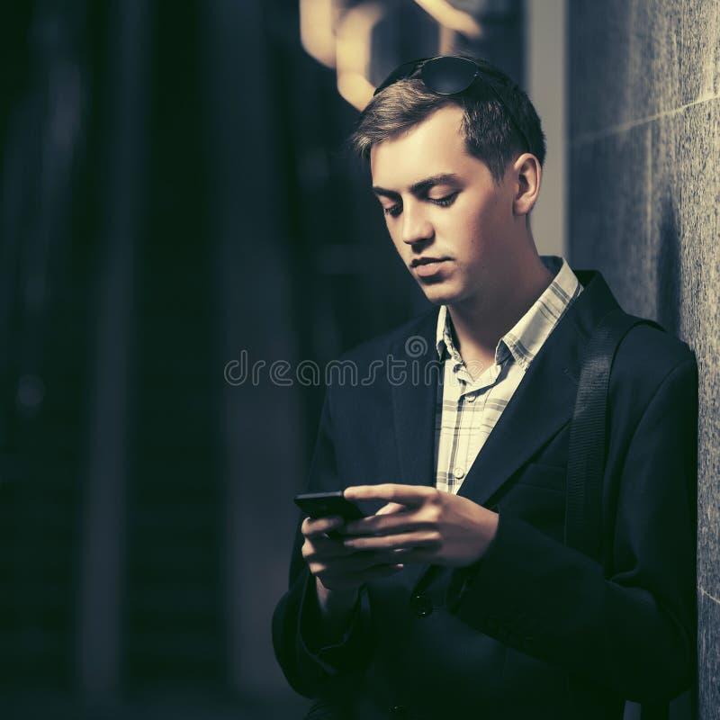 Giovane uomo bello facendo uso dello Smart Phone che sta alla parete fotografia stock libera da diritti