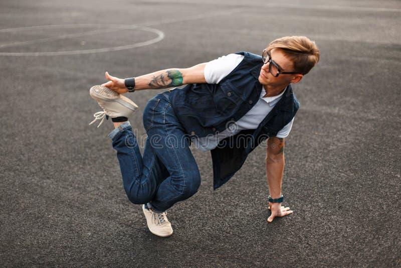 Giovane uomo bello in hip-hop alla moda di dancing del vestito dal denim immagini stock libere da diritti