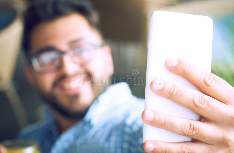 Giovane uomo bello sorridente con la barba e vetri che prendono selfie e tenuta del succo d'arancia mentre sedendosi in caffè immagine stock