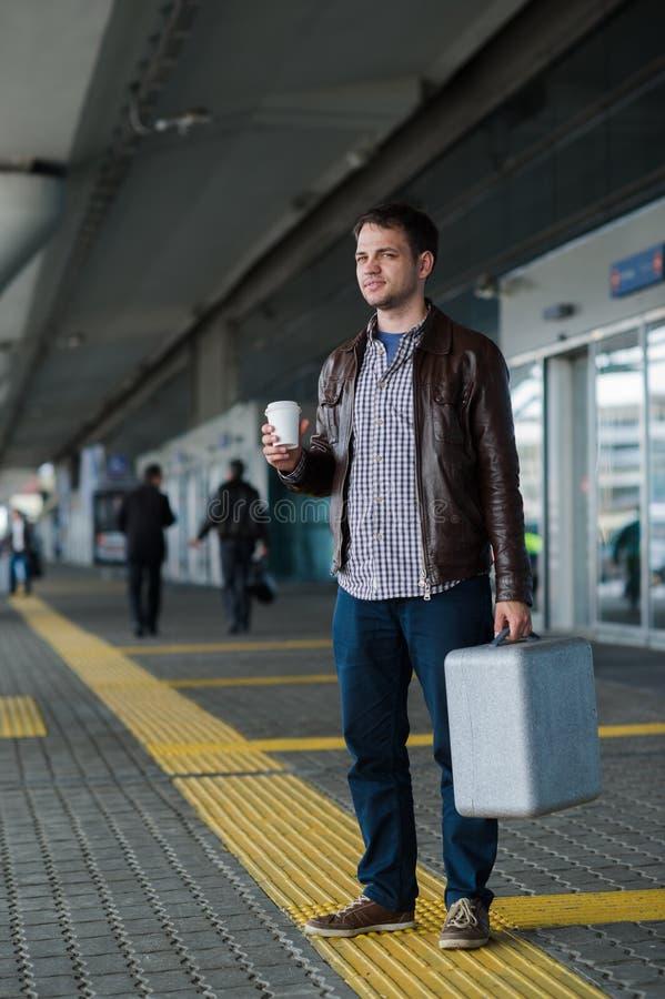 Giovane uomo bello sorridente felice del viaggiatore del ritratto integrale in 20s che lascia il terminale del salotto dell'aerop immagine stock