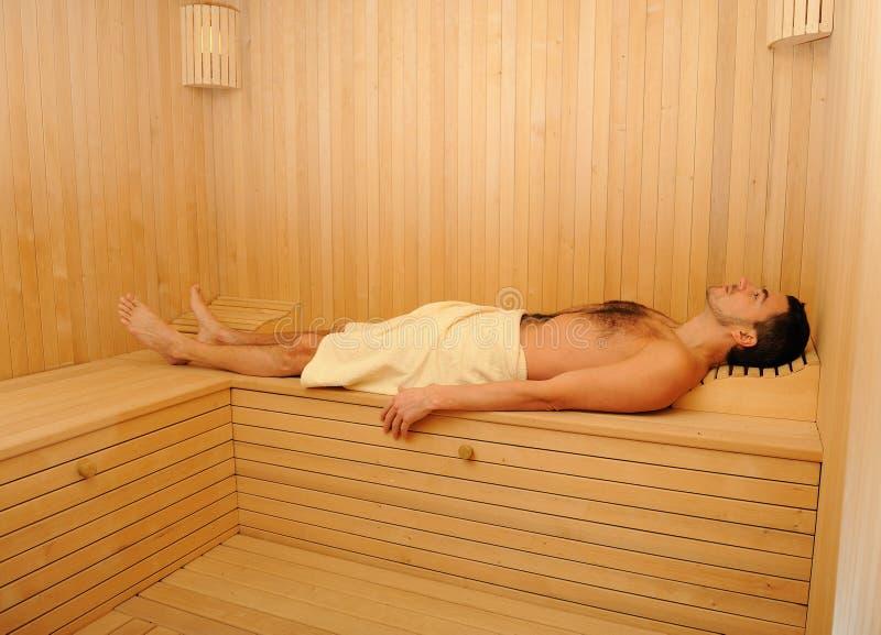 Giovane uomo bello in un tovagliolo che si distende nella sauna immagini stock