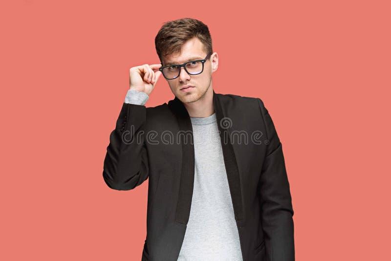 Giovane uomo bello in vestito nero e vetri isolati su fondo rosso fotografie stock libere da diritti