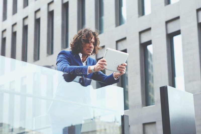 Giovane uomo ben vestito che per mezzo di una compressa digitale fotografia stock