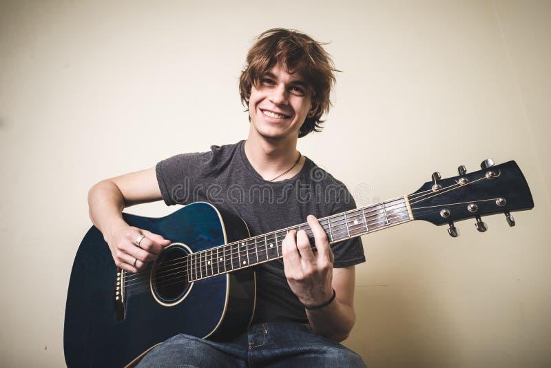 Giovane uomo biondo alla moda dei pantaloni a vita bassa che gioca chitarra immagine stock libera da diritti