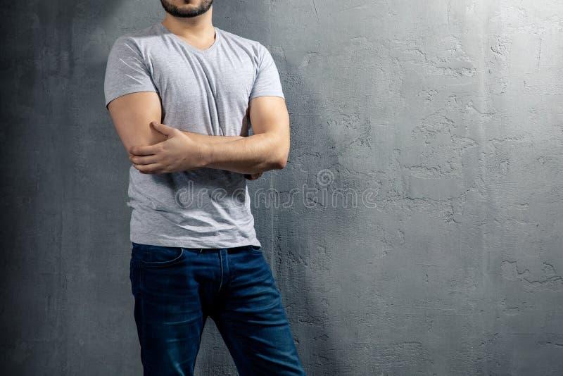 Giovane uomo in buona salute con la maglietta grigia su fondo concreto con copyspace per il vostro testo fotografie stock libere da diritti