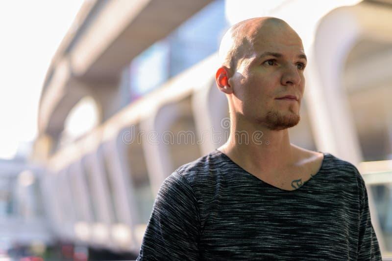Giovane uomo calvo bello che pensa contro l'esterno del centro commerciale dentro fotografie stock libere da diritti