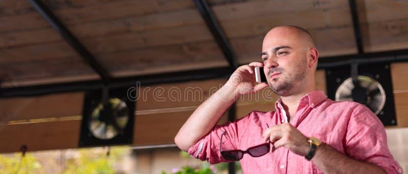 Giovane uomo calvo che parla sul telefono - scatola di lettera fotografia stock libera da diritti