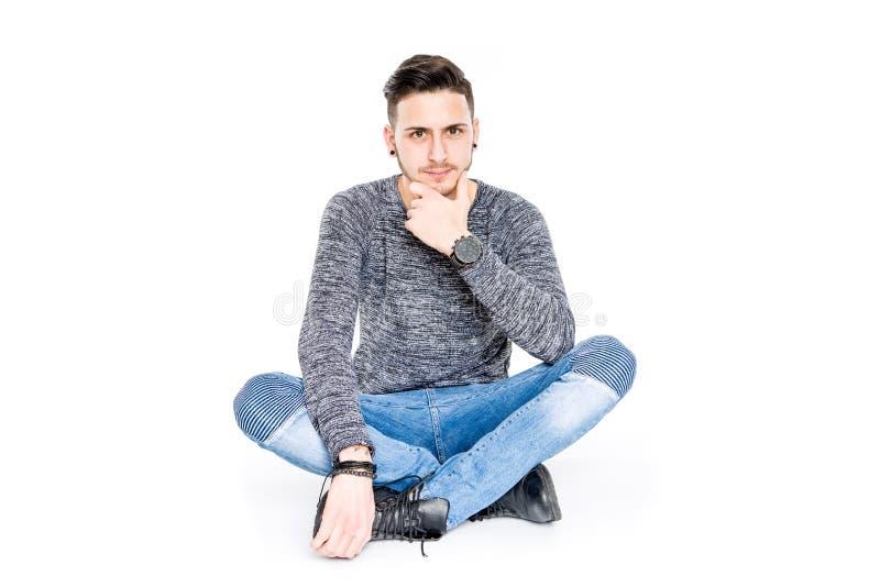 Giovane uomo castana casuale che si siede sul ritratto del pavimento che sorride - i fotografie stock libere da diritti