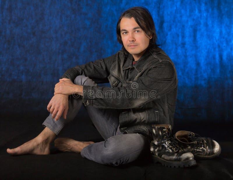 Giovane uomo casuale che si siede sul pavimento immagine stock libera da diritti