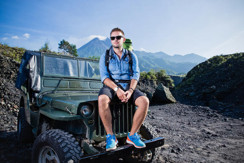 Giovane uomo caucasico bello che si siede sul cappuccio di una jeep, montagna fotografia stock libera da diritti
