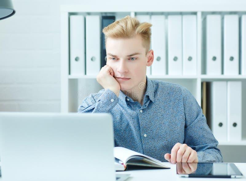 Giovane giovane uomo caucasico bello di affari che lavora al computer portatile alla scrivania fotografia stock libera da diritti