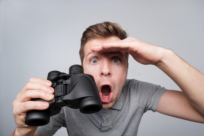 Giovane uomo caucasico che guarda con avanti la prova binoculare di vedere alcuni dettagli importanti fotografia stock libera da diritti