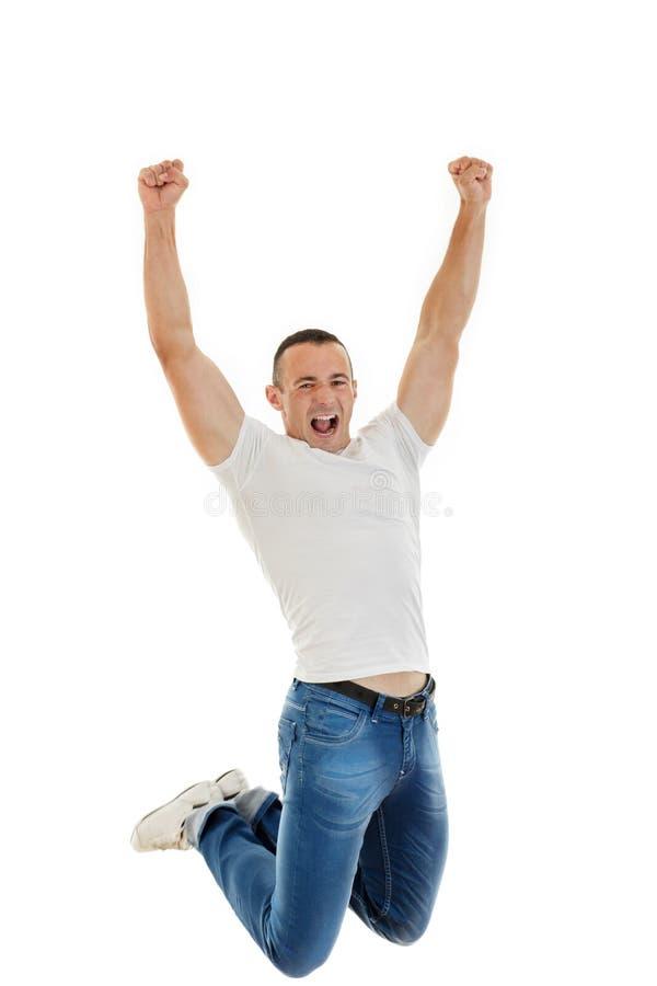 Giovane uomo caucasico felice casuale che serra i suoi pugni e salto fotografia stock libera da diritti