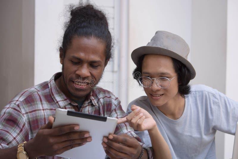 Giovane uomo creativo due discutere con il computer portatile e compressa, giovane asiatico e uomo di colore lavoranti con la com immagini stock