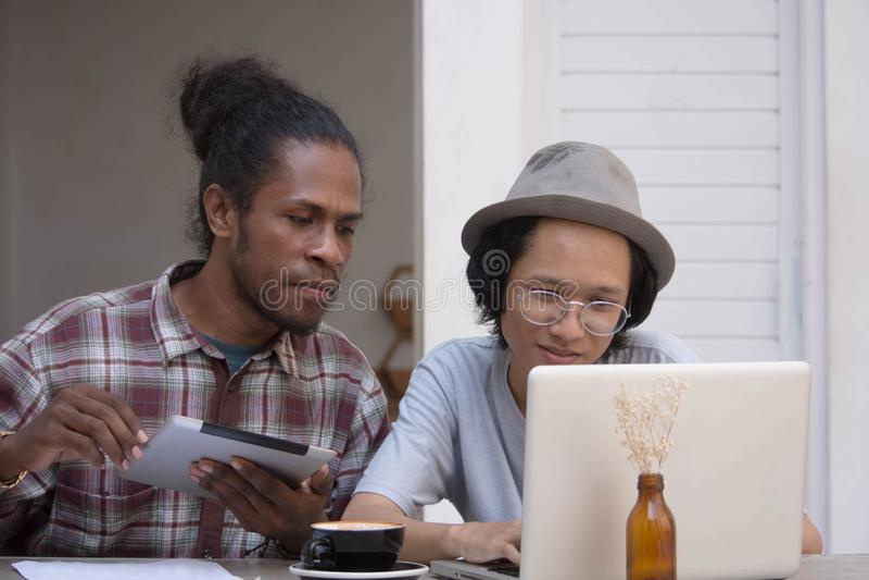 Giovane uomo creativo due discutere con il computer portatile e compressa, giovane asiatico e uomo di colore lavoranti con la com fotografie stock libere da diritti