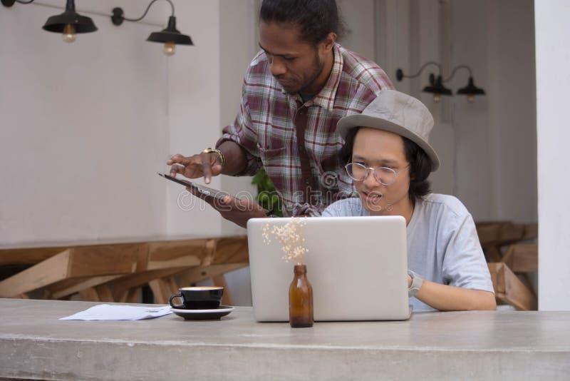 Giovane uomo creativo due discutere con il computer portatile e compressa, giovane asiatico e uomo di colore lavoranti con la com fotografia stock libera da diritti