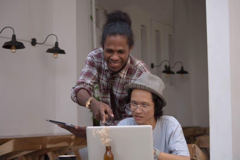 Giovane uomo creativo due discutere con il computer portatile e compressa, giovane asiatico e uomo di colore lavoranti con la com immagini stock libere da diritti