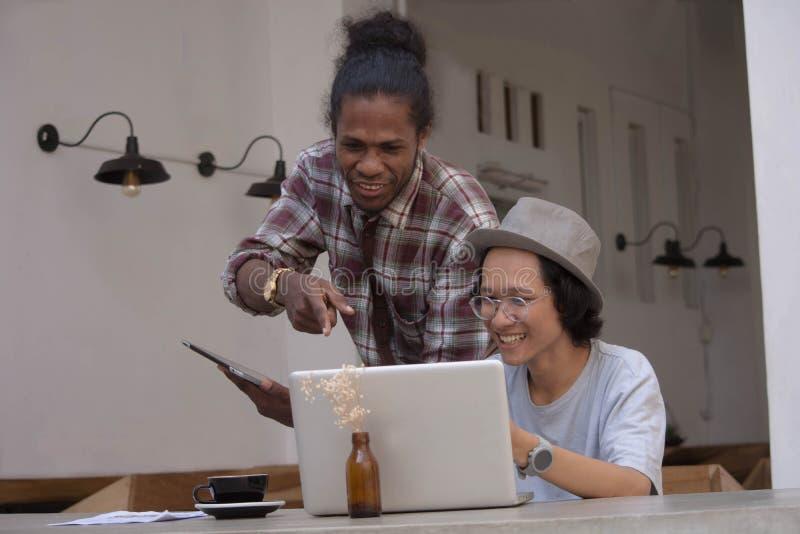 Giovane uomo creativo due discutere con il computer portatile e compressa, giovane asiatico e uomo di colore lavoranti con la com immagine stock libera da diritti