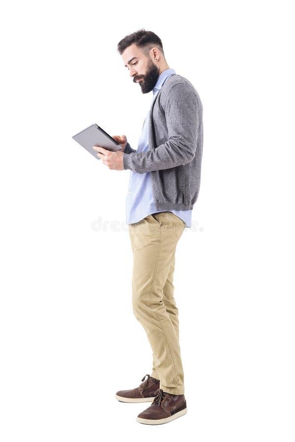 Giovane uomo d'affari adulto professionale che per mezzo ed esaminando del computer della compressa Vista laterale immagini stock