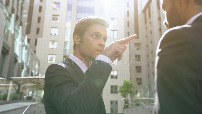 Giovane uomo d'affari aggressivo che fa sorveglianza voi gesto all'impiegato, capo immagini stock libere da diritti