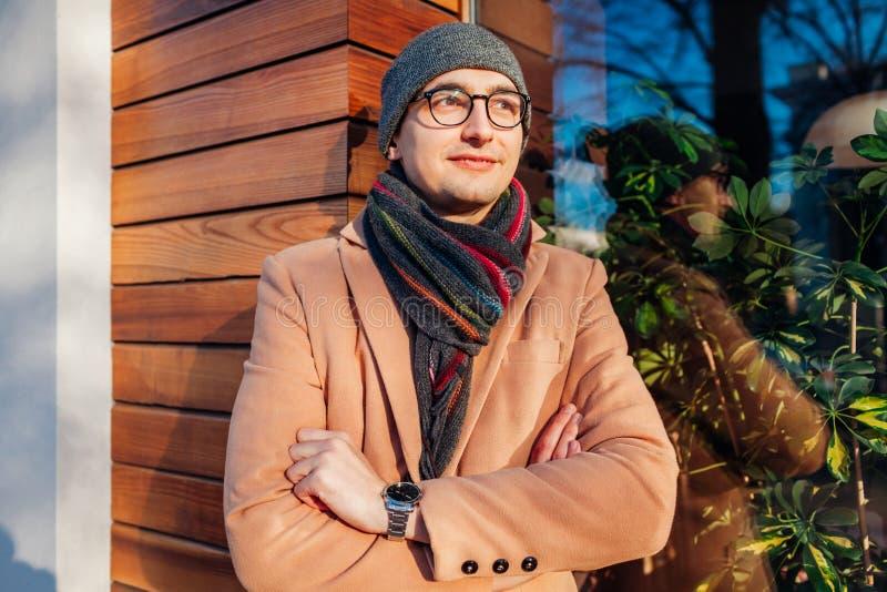 Giovane uomo d'affari alla moda che aspetta una riunione dal caff? Tipo bello che indossa i vestiti e gli accessori classici all' immagini stock