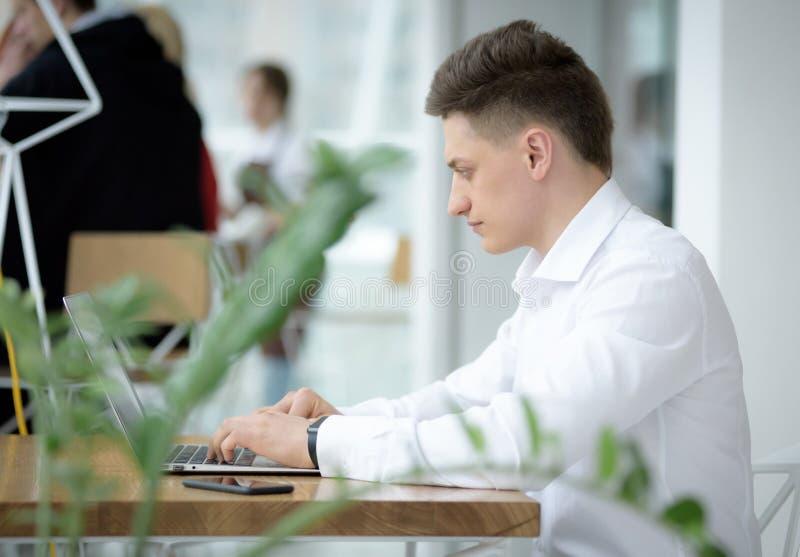 Giovane uomo d'affari alla moda dedicato che lavora al progetto in piccolo caffè accogliente fotografia stock