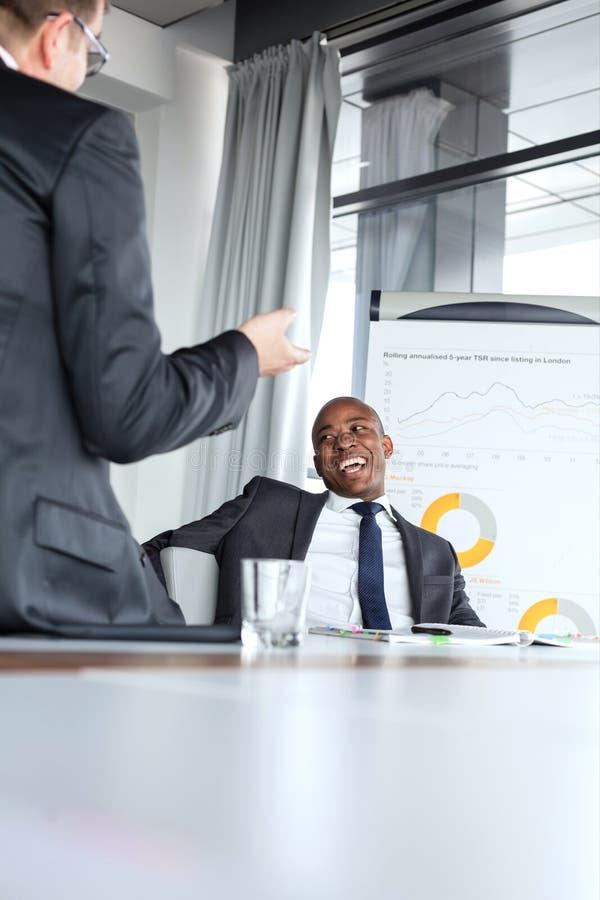 Giovane uomo d'affari allegro che parla con il collega maschio nella sala riunioni fotografia stock