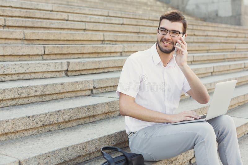 Giovane uomo d'affari allegro facendo uso del computer portatile e della fabbricazione della chiamata sullo sta fotografia stock