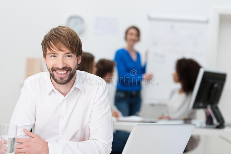 Giovane uomo d'affari amichevole che si siede al suo scrittorio immagini stock