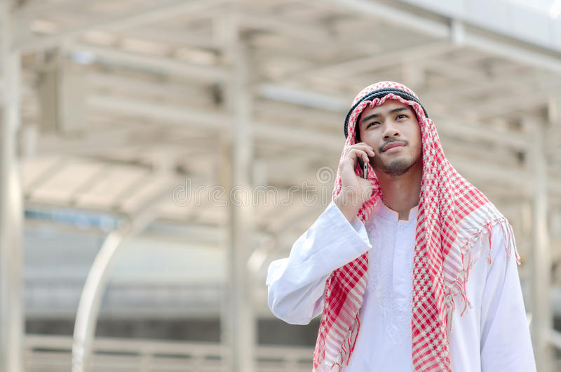 Giovane uomo d'affari arabo facendo uso del telefono cellulare mentre camminando nella c immagini stock